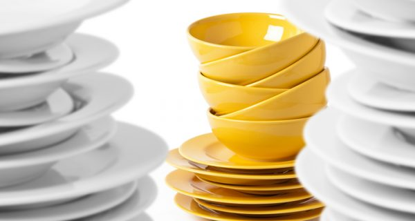 A stack of yellow bowls and plates isolated on white. Selective focus on yellow bowls, blurred white plates.
